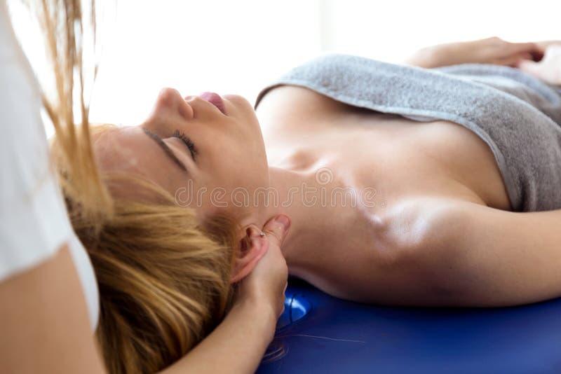 对脖子治疗做的年轻生理治疗师患者在物理疗法屋子 库存图片