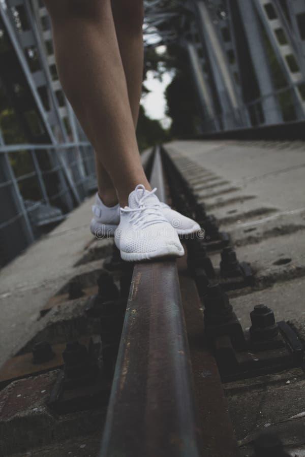 对膝盖的女性腿,在白色运动鞋,在路轨的立场 免版税库存照片