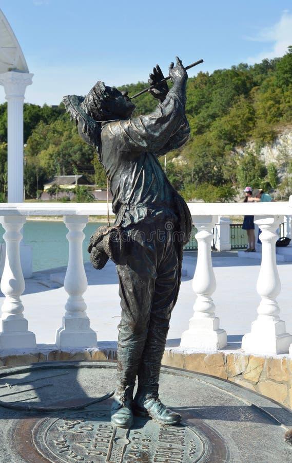 对苏联歌手牧羊人Potekhina骨头的角色的列昂尼德Utesov的纪念碑从苏联电影快活的家伙的 库存图片