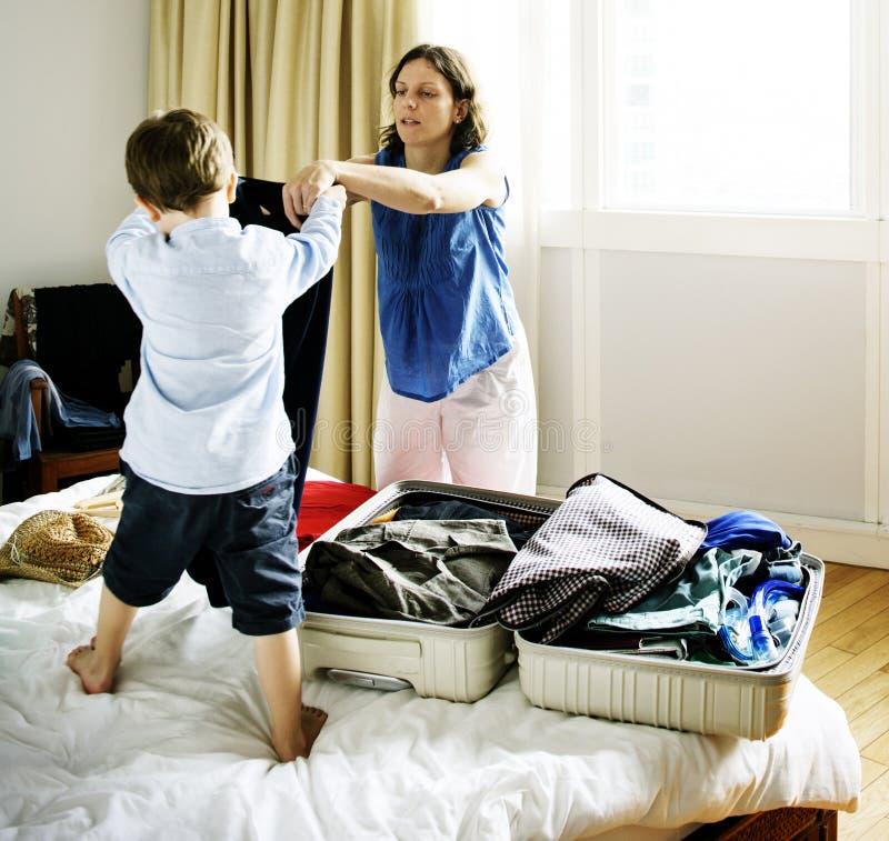 对行李的妈妈和儿子帮助的组装衣物旅行的 免版税图库摄影