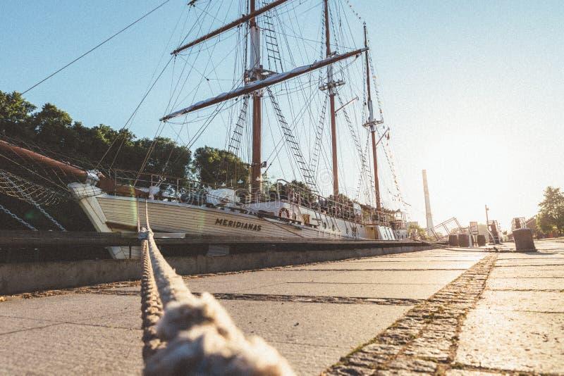对被停泊的船的绳索在日出光  免版税库存图片