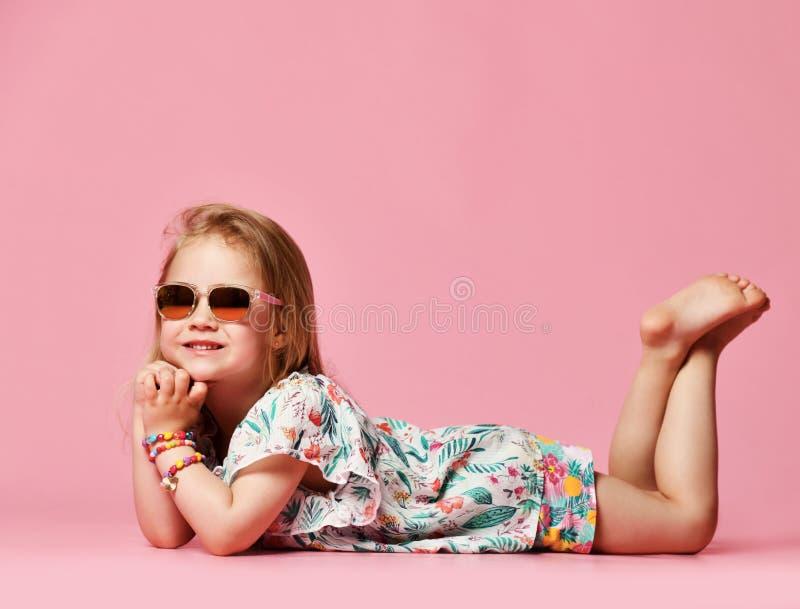对说谎在演播室的地板上的边的女孩童颜夏天衣裳的在桃红色背景一的太阳镜 库存图片