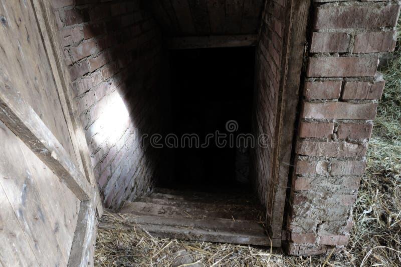 对谷仓的食物地下室的鬼和可怕黑暗的入口在乡下 库存照片