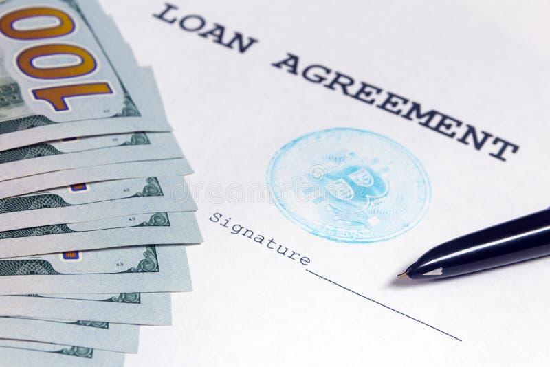 对贷款协议的署名地方的钢笔点与蓝色bitcoin的盖印 附近一百美元bil 库存图片