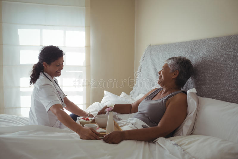 对资深妇女的女性医生服务早餐在床上 免版税库存照片
