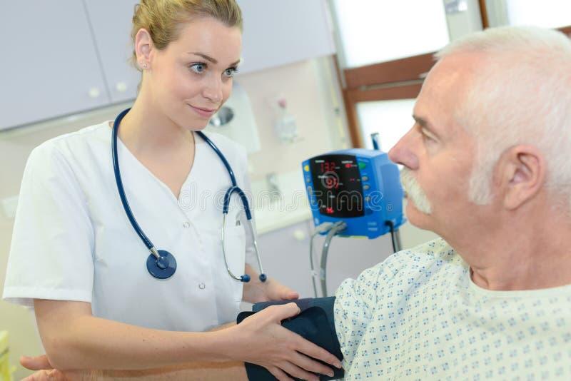 对资深患者的女性医生测试血压 免版税库存照片