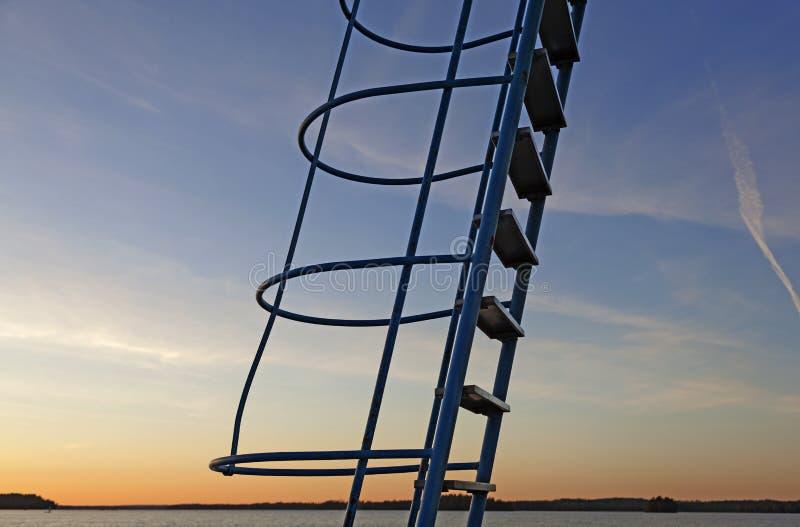 对跳跃的塔的梯子在日落 库存照片