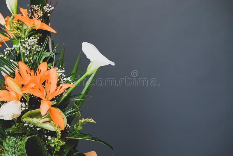 对边的花的布置花束与灰色演播室背景拷贝空间 与灰色消极空间的花卉概念背景 库存照片