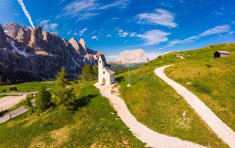 对道路的美好的空中全景向小白色教堂圣毛里齐奥和多洛米蒂山风景 免版税图库摄影