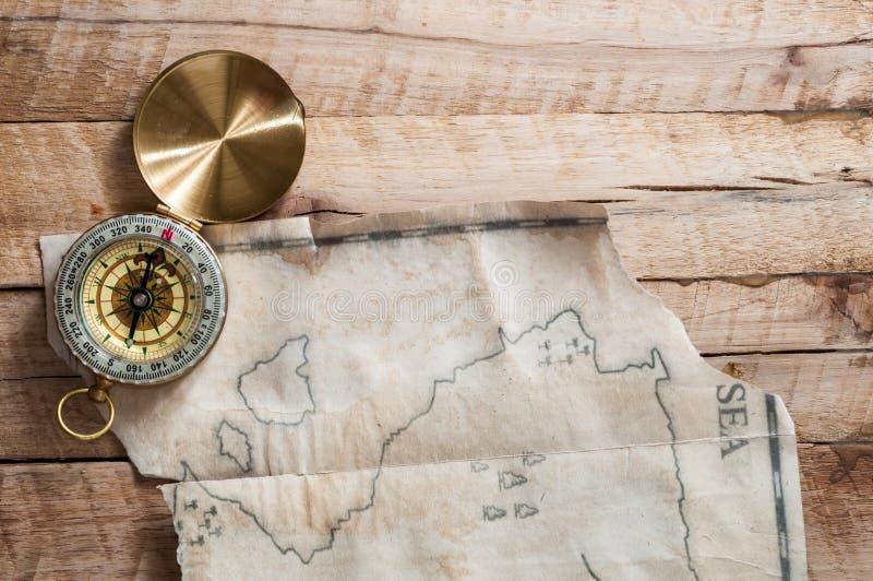 对金指南针的顶视图在有假手工制造葡萄酒地图的木书桌上 库存照片