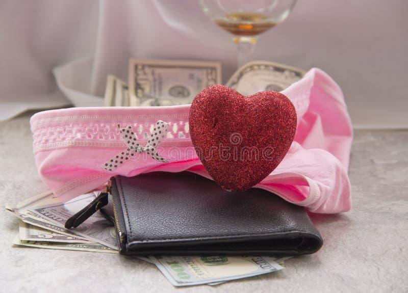 对金钱的爱是卖淫 被弄皱的板料、一在她的内衣的杯酒和金钱是性费 免版税库存照片