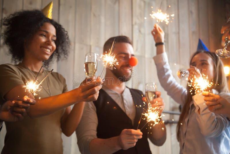 对闪烁发光物庆祝负的非洲和白种人朋友新 免版税库存照片