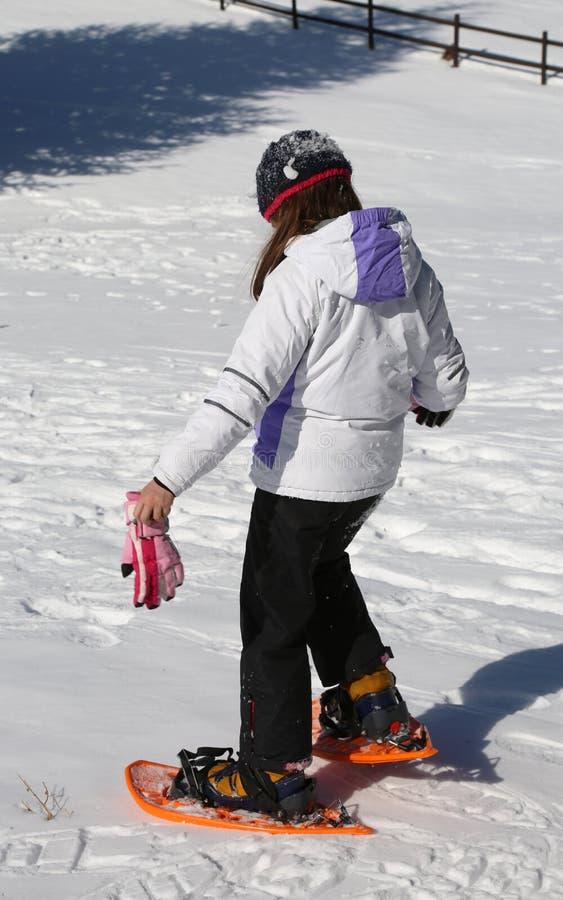 对雪靴的小女孩尝试 库存照片