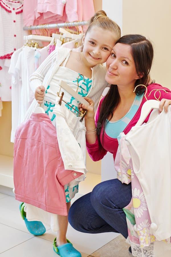 对面颊的微笑的女孩和母亲面颊在服装店 免版税库存照片
