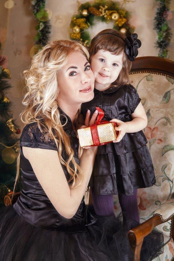 对面颊的母亲和女儿面颊在圣诞节 库存图片