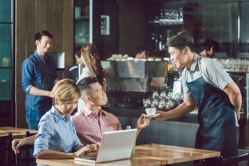 对顾客的侍者服务的咖啡 库存图片