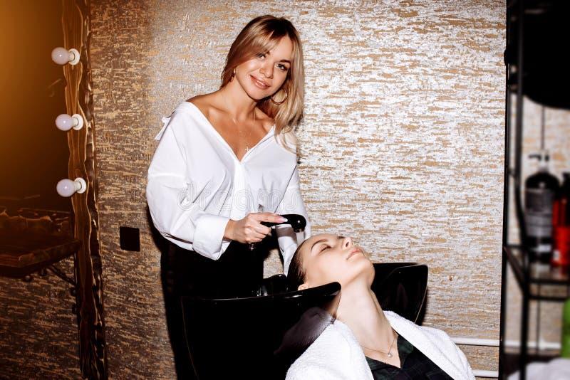 对顾客的发式专家洗涤的头发在做发型前 应用在妇女的头发的美发师养育的面具在秀丽 免版税库存照片