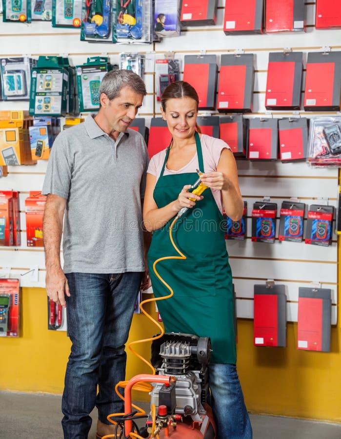 对顾客的女推销员解释的空气压缩机 免版税库存照片