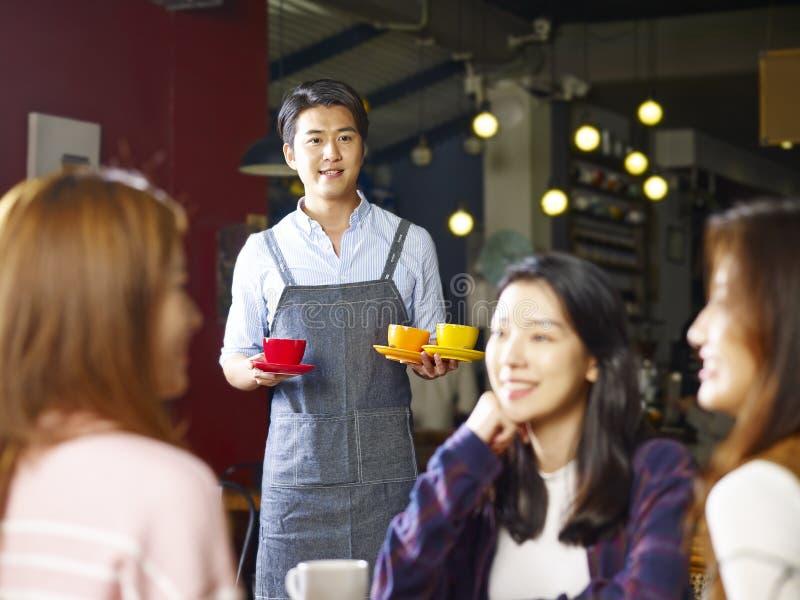 对顾客的年轻人微笑的亚洲侍者服务咖啡 免版税库存照片