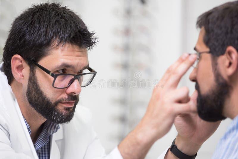 对顾客的眼镜师提供的玻璃测试和尝试的 显示耐心透镜的眼科医生在眼镜商店 免版税库存照片