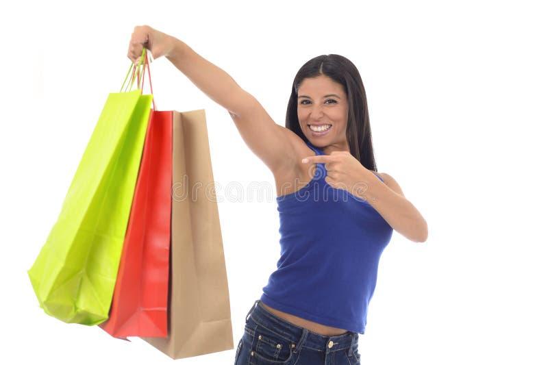 对颜色购物袋微笑负的年轻愉快和美丽的西班牙妇女被激发隔绝 库存照片