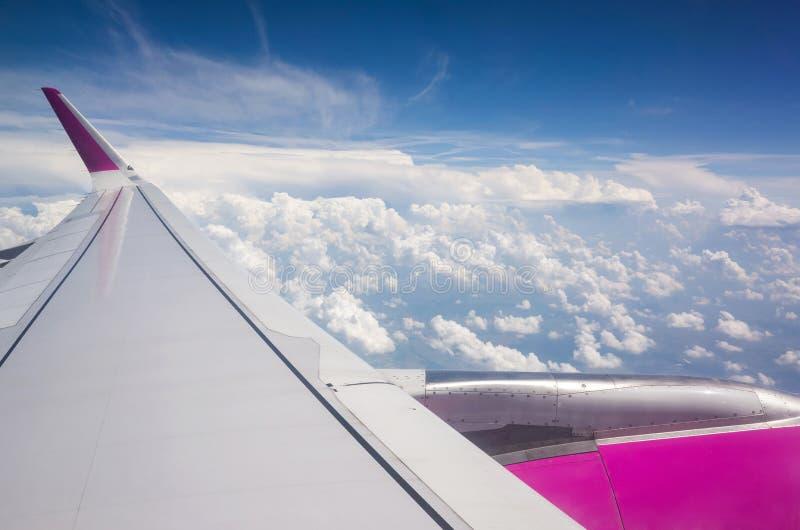 对飞机翼和云彩的看法在舷窗窗口外面 免版税库存图片