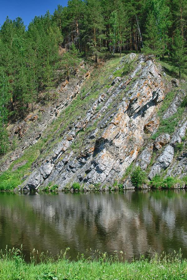 对高岩石的令人惊讶的看法在仍然河有森林背景 库存图片