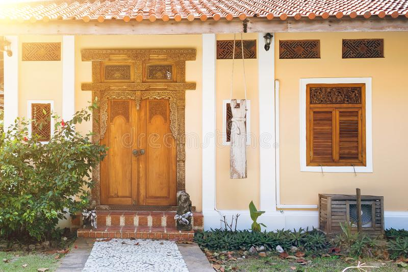 对黄色房子的入口有木被雕刻的快门的 与被雕刻的样式的老木门 导致台阶的石道路 库存图片