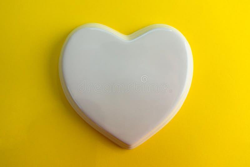 对黄色紫罗兰色背景的白色光滑的瓷心脏;婚礼;喜帖;爱笔记 免版税库存照片