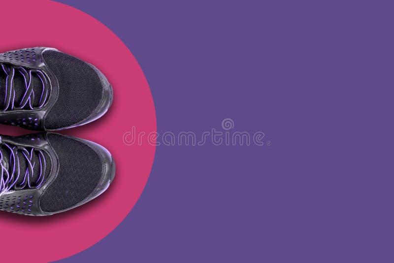 对黑鞋子,运动鞋在桃红色圈子的中心在年紫外的时兴的颜色的背景的 免版税库存图片