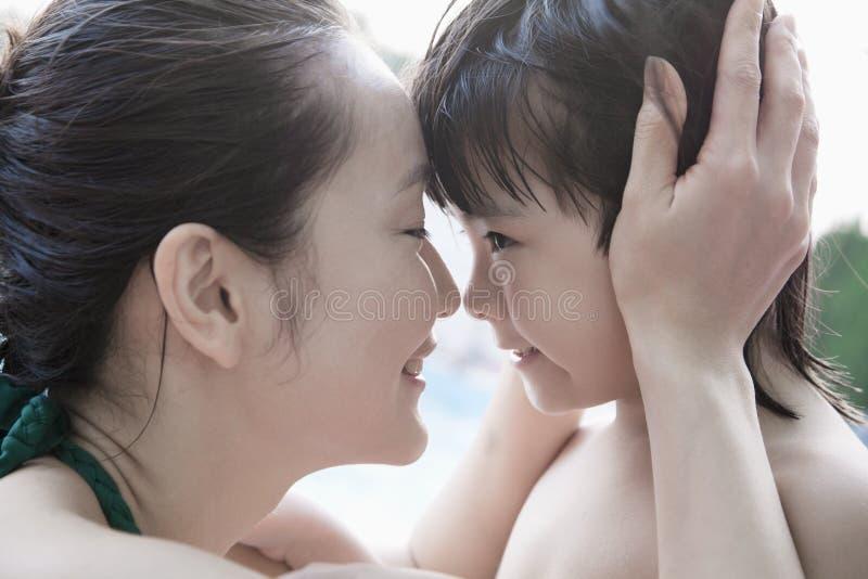 对负微笑的母亲和的儿子拥抱和顶头由水池 免版税库存照片