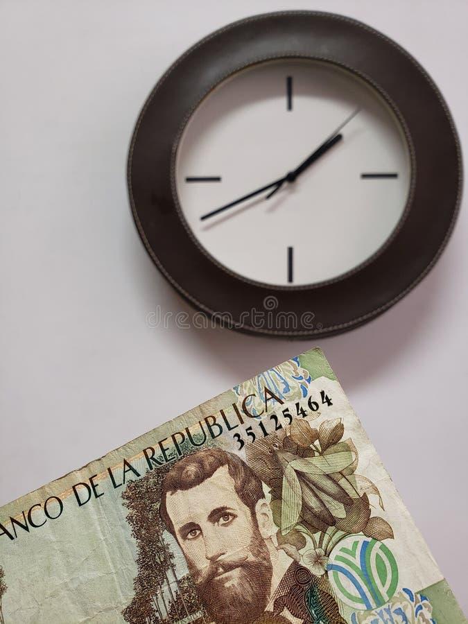 对5000比索和背景哥伦比亚的钞票的方法与一个圆壁钟 免版税库存照片