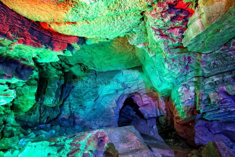 对洞的入口在土地下绘了明亮的意想不到的颜色 免版税库存图片