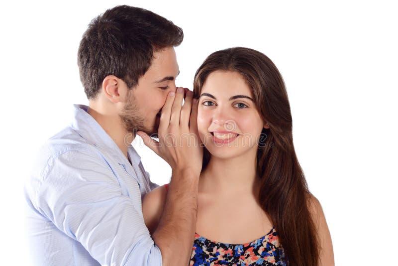 对他的女朋友的人耳语的秘密 免版税图库摄影