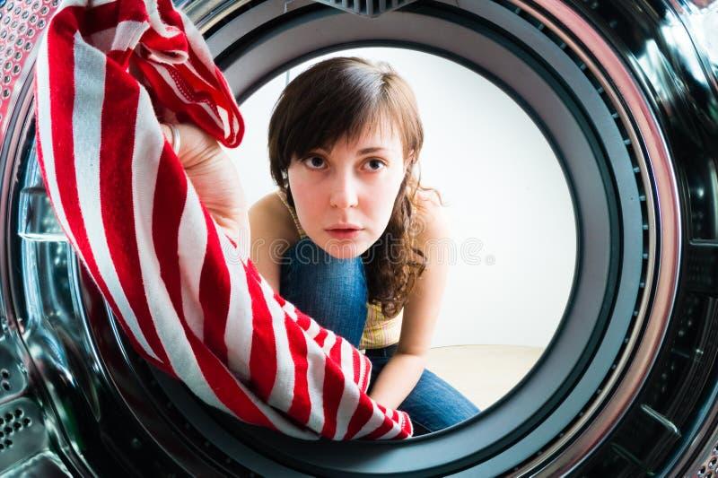 对洗衣机的滑稽的女孩装货衣裳 库存图片