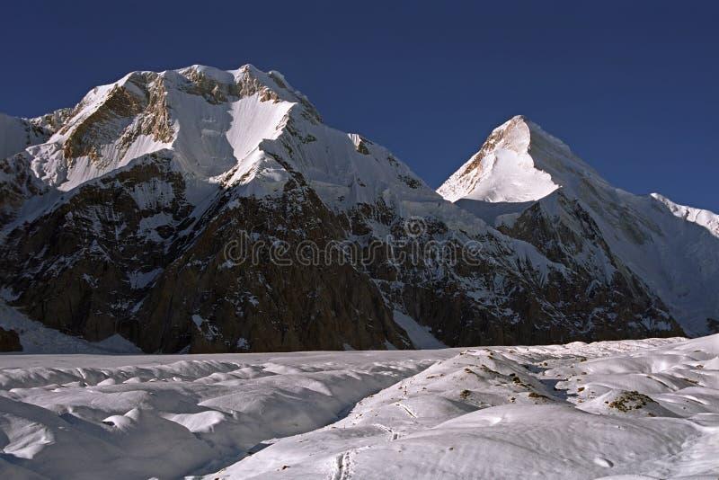 对Chapaev峰顶6371m的早晨视图在左边和汗腾格里峰峰顶6995m 库存图片
