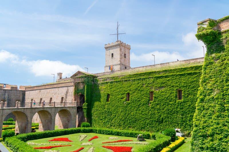 对Montjuic城堡的入口横跨前护城河,现在干燥和种植作为分配为花坛的区域 免版税库存图片