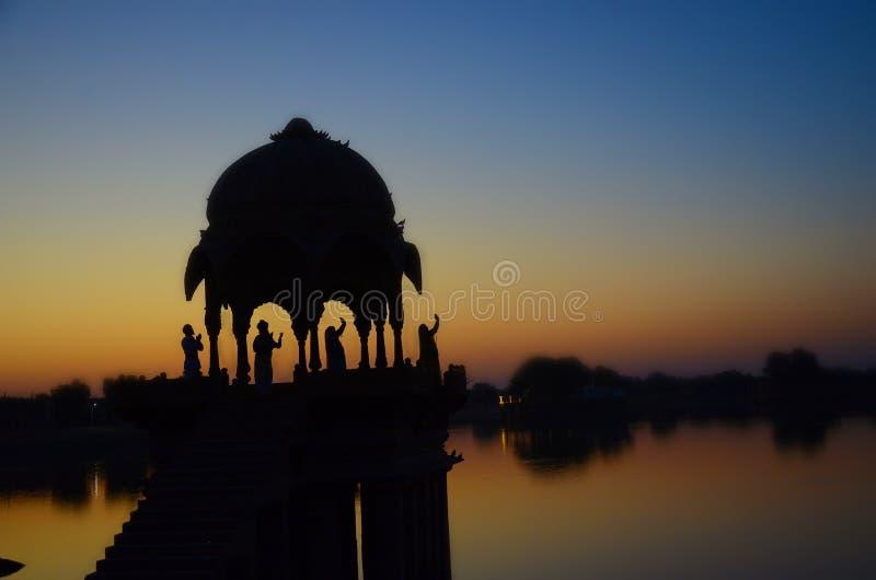 寺庙剪影在Gadi Sagar湖的有四人的 库存照片