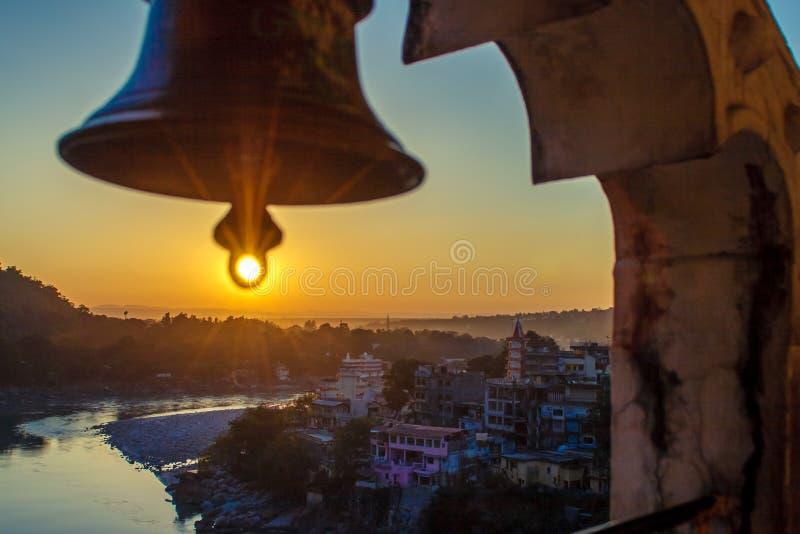 从寺庙的看法在河甘加和拉克什曼Jhula桥梁的巨大的响铃下在日落 瑞诗凯诗 免版税库存照片