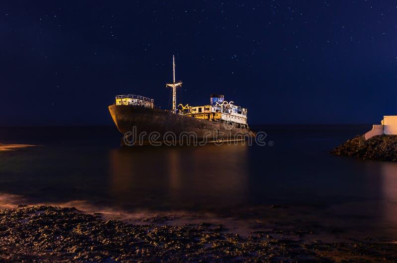 寺庙霍尔在阿雷西费,兰萨罗特岛附近的船击毁夜视图  免版税库存图片