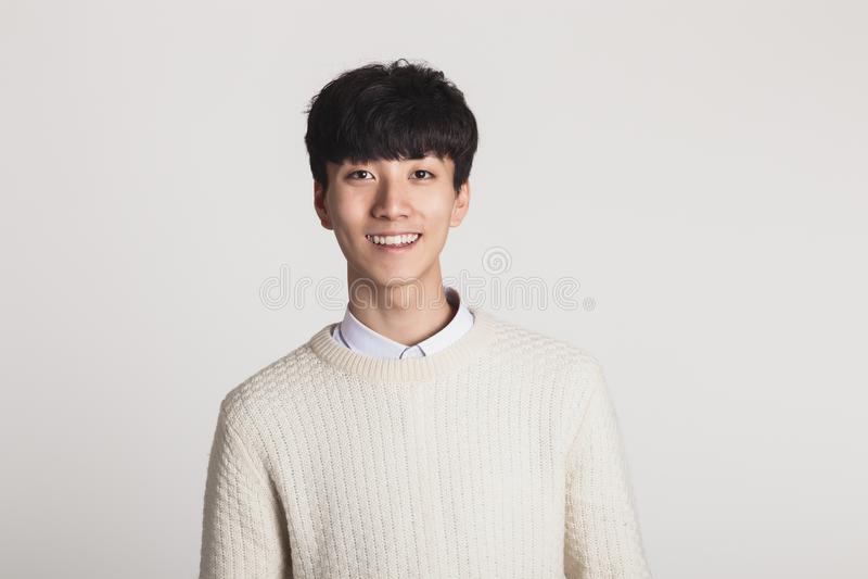 寻找与确信的微笑的一个亚裔年轻人的演播室画象一台照相机 免版税库存图片