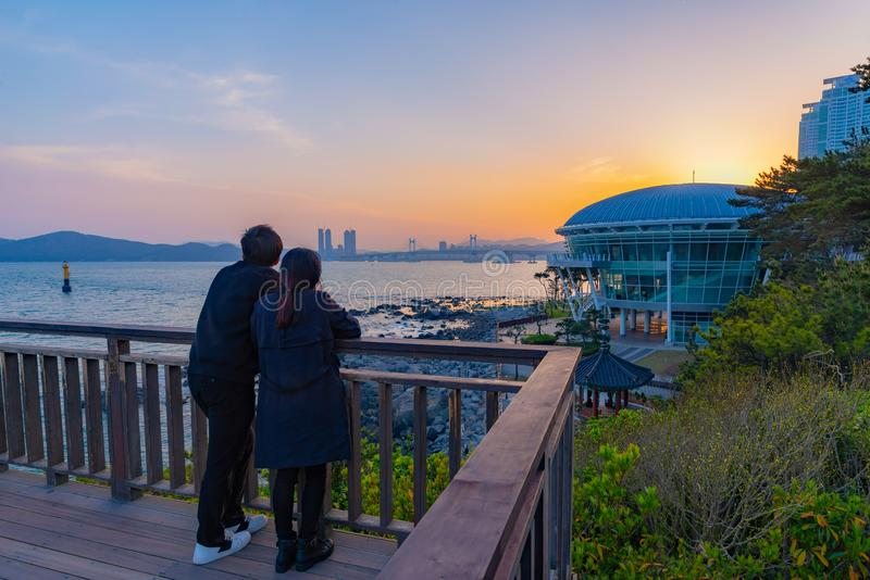 寻找与Nurimaru亚太经合议院的夫妇浪漫日落和海视图 免版税库存照片