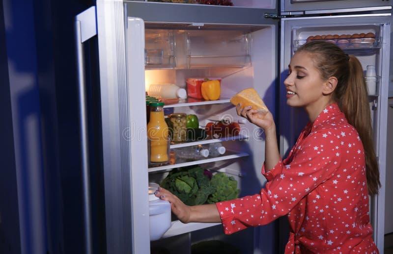 寻找在冰箱的年轻女人食物 免版税库存图片