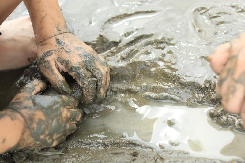 寻找在海底泥的男孩蜗牛壳 免版税库存照片
