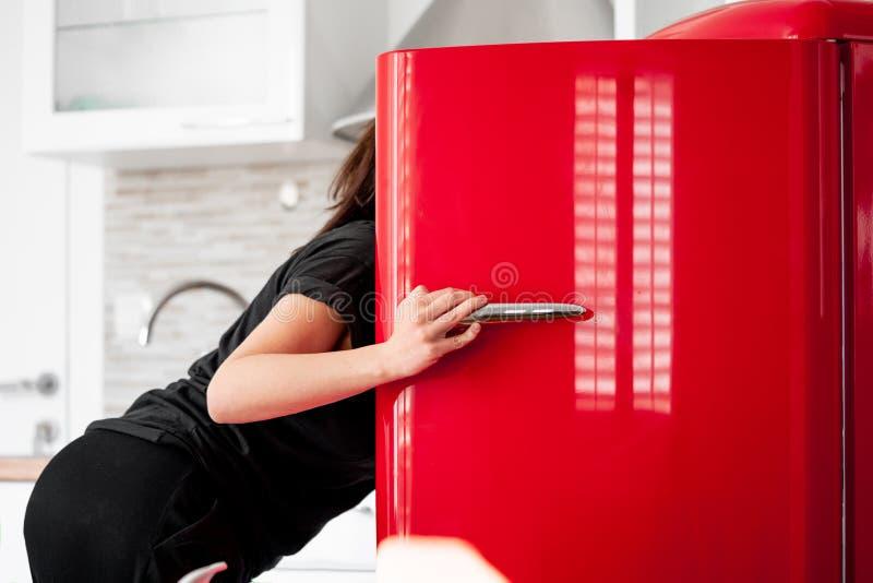 寻找在红色冰箱的妇女食物在现代明亮的公寓 免版税库存照片