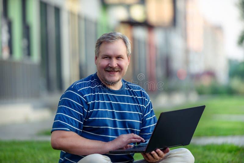 寻找在膝上型计算机的愉快的人网上内容坐草坪在城市 库存图片