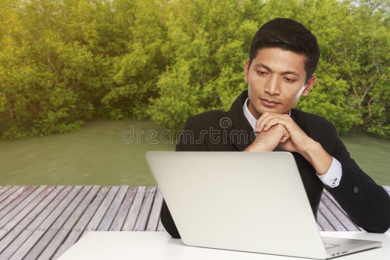 寻找在计算机显示器的年轻商人一个工作和 免版税库存照片
