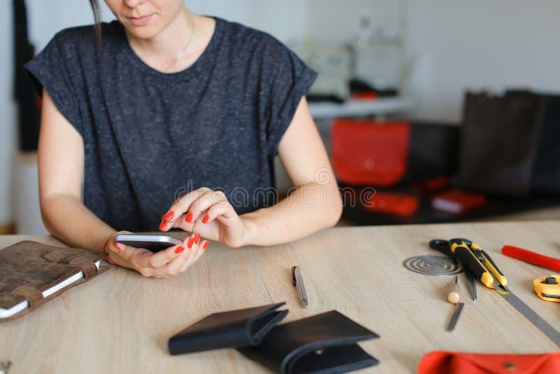 寻找想法的女性由智能手机在手工制造笔记本附近在皮革工作室 免版税库存照片