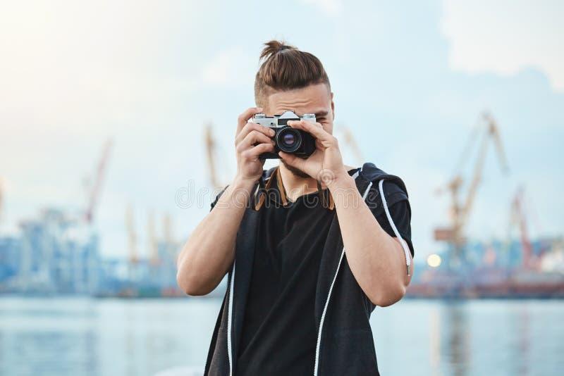 寻找最佳的射击 可爱的都市摄影师画象有拍照片的葡萄酒照相机的临近海,走 免版税库存图片