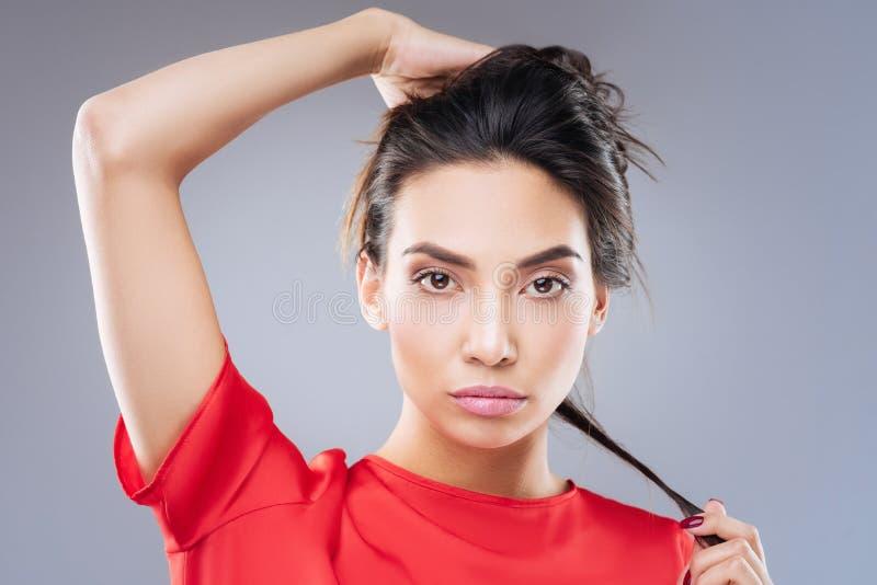 寻找最适当的发型的美丽的少妇 库存照片